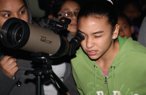 Girl looking through telescope, other children waiting