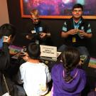 teen volunteers work with museum visitors on spectroscopy project