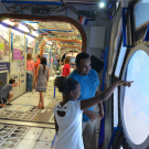 family looking out cupola in ISS exhibit