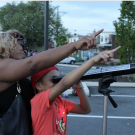 Mother and son look through telescope on street; both point at what they are looking at
